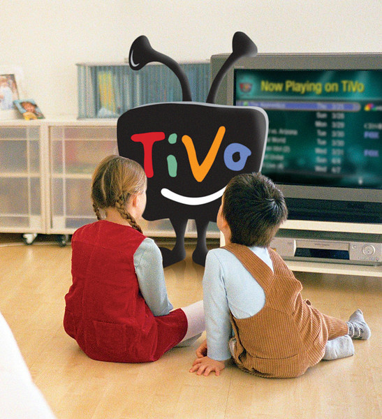 Lttle boy and girl sitting together on parquet floor looking at tv, rear view