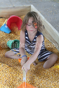 Autumn Murley digs through the corn pool in the Family Fun Barn Thursday afternoon at the Calhoun County Expo. GRAPHIC-ADVOCATE PHOTO/ERIN SOMMERS