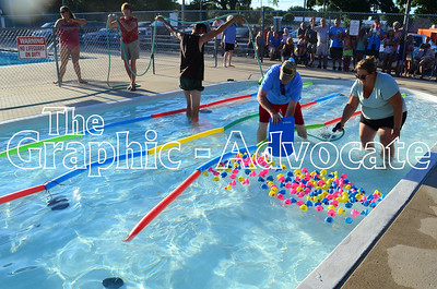 Opportunity Living employees and volunteers move rubber ducks along through a miniature race course in the Rockwell City baby pool Saturday night. Community members paid $5 per duck for a chance to win a cash prize. GRAPHIC-ADVOCATE PHOTO/ERIN SOMMERS