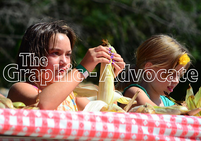 Two girls shuck corn during the sweet corn eating contest Saturday at Rockwell City's Sweet Corn Daze. GRAPHIC-ADVOCATE PHOTO/ERIN SOMMERS