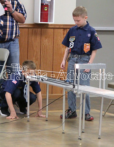 Cub Scouts Carter Hawkins and Elijah Wilson wait for their cars to come down the racetrack Sunday during the annual Pinewood Derby at the Calhoun County Expo building. GRAPHIC-ADVOCATE PHOTO/ERIN SOMMERS