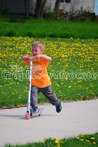 A boy scoots along the route for the Walk for Water Saturday. GRAPHIC-ADVOCATE PHOTO/ERIN SOMMERS