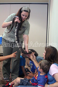Parents and children had a chance to touch a ball python, held by Blank Park Zoo's Samantha Dunn, Friday moring at the Rockwell City Public Library. GRAPHIC-ADVOCATE PHOTO/ERIN SOMMERS