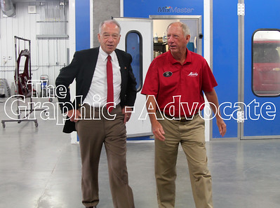 U.S. Sen. Charles Grassley, left, and Gus Macke walk through Macke Motors in Lake City Tuesday afternoon. GRAPHiC-ADVOCATE PHOTO/ERIN SOMMERS