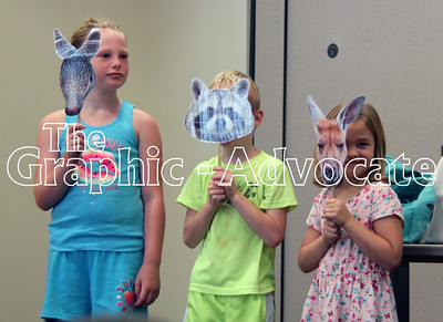 Children hold animal masks during an exercise Friday afternoon at the Rockwell City Public LIbrary. GRAPHIC-ADVOCATE PHOTO/ERIN SOMMERS