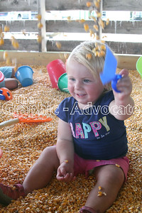 Madalynn Wahl, 1, throws corn in the Family Fun Barn at Calhoun County Expo Friday. GRAPHIC-ADVOCATE PHOTO/ERIN SOMMERS