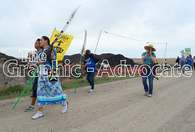 Marisa Cummings, left, carries a sign down Red Oak Avenue during a protest of the Dakota Access pipeline. GRAPHIC-ADVOCATE PHOTO/ERIN SOMMERS