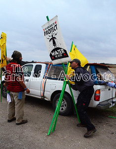 David Solnit, right, hands out protest banners to protesters on Red Oak Avenue. GRAPHIC-ADVOCATE PHOTO/ERIN SOMMERS