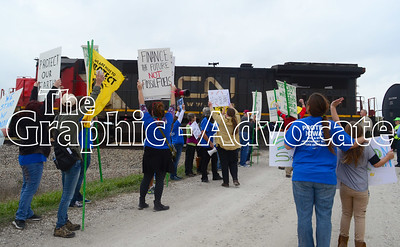 Protestors wave signs at a passing train on Red Oak Avenue Saturday afternoon. GRAPHIC-ADVOCATE PHOTO/ERIN SOMMERS