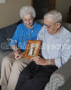 Mary and Dale Sexton look at their wedding photo at their Sunnyview apartment Friday. They were married Jan. 4, 1947, in Rockwell City. GRAPHIC-ADVOCATE PHOTO/ERIN SOMMERS