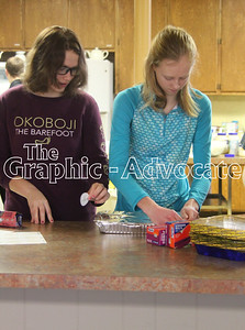 Alli Morenz, left, and Megan Decker prepare food to be frozen, as part of an Interact community service project last month. GRAPHIC-ADVOCATE PHOTO/ERIN SOMMERS