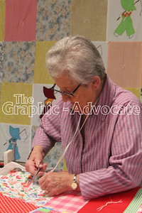 Pat Maunu trims tied knots on a quilt Jan. 23. GRAPHIC-ADVOCATE PHOTO/ERIN SOMMERS