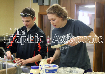 Nic Englin, left, and Allison Birks clean up after making casseroles for an Interact service project. GRAPHIC-ADVOCATE PHOTO/ERIN SOMMERS