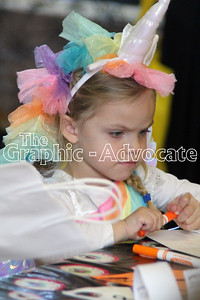 Alivia Lynch, 3, colors a picture at the Lohrville Harvest Party Sunday. Volunteers with community groups put on the event each year. GRAPHIC-ADVOCATE PHOTO/ERIN SOMMERS