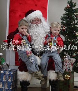 Joseph and Isaack Schultz, both 4, smile while sitting on Santa's lap Saturday in Lake City. GRAPHIC-ADVOCATE PHOTO/ERIN SOMMERS