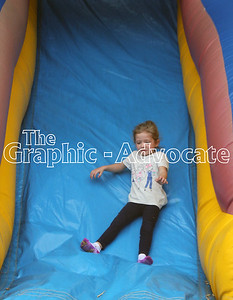 Payson Stephenson comes down a bouncy slide Sunday morning during Lake City's annual Fall Fest. GRAPHIC-ADVOCATE PHOTO/ERIN SOMMERS