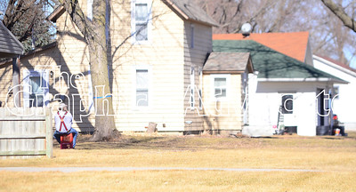 A Rockwell City resident sits in his yard Feb. 21, watching as law enforcement officers tried to talk Paul Goodman out of Goodman's Grant Street home. GRAPHIC-ADVOCATE PHOTO/ERIN SOMMERS