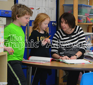 Kindergarten teacher Kris Nicholson works with Aiden Melody, left, and Blair Gulbranson, center, during journal time Feb. 21. The SCC school board opted to keep transitional kindergarten for next year, instead of putting all 5-year-old students in kindergarten. GRAPHIC-ADVOCATE PHOTO/ERIN SOMMERS