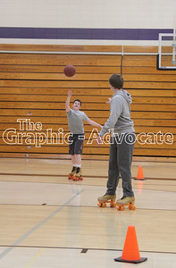 Brayden Hawkins throws a basketball to a classmate while rollerskating during gym class March 6. GRPAHIC-ADVOCATE PHOTO/ERIN SOMMERS