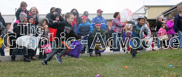 Children make a racing start toward a yard of Easter eggs at Opportunity Living Saturday morning. GRAPHIC-ADVOCATE PHOTO/ERIN SOMMERS