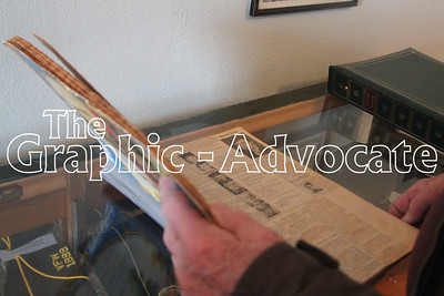 Gary Fahan pages through a scrapbook filled with World War II news clippings. The scrapbook is one of many military items on display at the Lake City Community Center. GRAPHIC-ADVOCATE PHOTO/ERIN SOMMERS