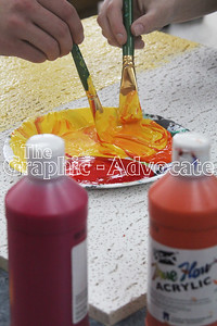 Students mix paint to achieve the right orange for a sunset painting on a ceiling tile. GRAPHIC-ADVOCATE PHOTO/ERIN SOMMERS