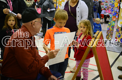 Dale Gentry hands a sketch to a young observer during Wednesday's Preschool Art Show at South Central Calhoun Elementary School. GRAPHIC-ADVOCATE PHOTO/ERIN SOMMERS