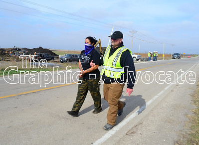 A Dakota Access security guard walks a protester to law enforcement officers Saturday afternoon in Sigourney Avenue, east of Rockwell City. GRAPHIC-ADVOCATE PHOTO/ERIN SOMMERS
