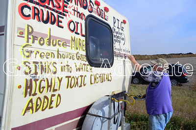 Sandy Eccles of Missouri paints a protest message on her motor home near the Dakota Access pipeline construction site on Sigourney Avenue Saturday afternoon. Eccles grew up in Manson. GRAPHIC-ADVOCATE PHOTO/ERIN SOMMERS