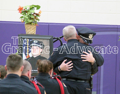 Urbandale Police Chief Ross McCarty hugs Officer Brady Farrington during Officer Justin Martin's funeral Tuesday. GRAPHIC-ADVOCATE PHOTO/ERIN SOMMERS