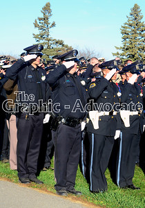 Police officers salute as Urbandale Officer Justin Martin's casket is brought in to the cemetery Tuesday afternoon. GRAPHIC-ADVOCATE PHOTO/ERIN SOMMERS