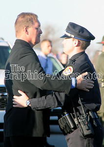 Urbandale Police Officer Brady Farrington embraces Randy Martin Tuesday afternoon at Rosehill Cemetery. GRAPHIC-ADVOCATE PHOTO/ERIN SOMMERS