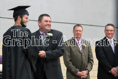 Chase Mosbach, left, accepts his diploma from South Central Calhoun School Board President Ron Maulsby, while board members Roger McKinney and Brad Assman watch. GRAPHIC-ADVOCATE PHOTO/ERIN SOMMERS