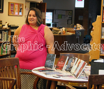 Author d. Nichole King stands by a display of several of her books in the J.J. Hands Library in Lohrville Thursday night. King spoke about her books and how she got into writing. GRAPHIC-ADVOCATE PHOTO/ERIN SOMMERS
