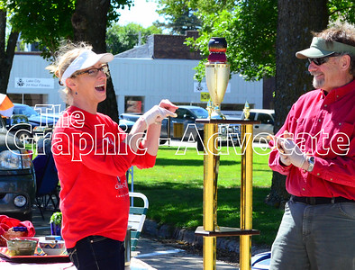 Robin Qualy, left, and Paul Qualy, react to the Lake City chili cookoff trophy Sunday afternoon on the town square. Judges selected Qualy's Tres Frijoles chili as the winning entry in the annual cookoff. GRAPHIC-ADVOCATE PHOTO/ERIN SOMMERS