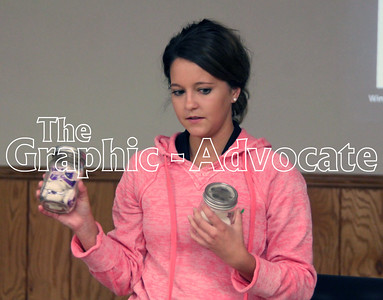 Presley Herrig of New Co-op in Lohrville holds up jars of marshmallows and dishwasher detergent, to illustrate how similar dangerous household chemicals can look to food. GRAPHIC-ADVOCATE PHOTO/ERIN SOMMERS