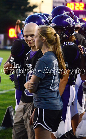 Jacy McAlexander, left, speaks with a football team manager Friday night during a South Central Calhoun Titans game in Lake City. GRAPHIC-ADVOCATE PHOTO/ERIN SOMMERS
