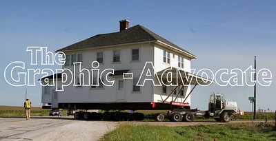 A truck pulls a two-story farmhouse around a corner, turning west on 290th Street from Highway 4, south of Rockwell City. GRAPHIC-ADVOCATE PHOTO/ERIN SOMMERS