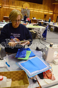Marcia Alhrichs of Rockwell City lays out fabric she will use to make a cloth placemat that matches a paper placement she found. GRAPHIC-ADVOCATE PHOTO/ERIN SOMMERS
