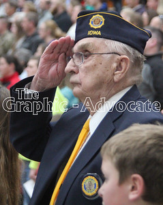 A veteran salutes during the Pledge of Allegiance Friday at South Central Calhoun Middle School. More than 110 veterans attended the program. GRAPHIC-ADVOCATE PHOTO/ERIN SOMMERS