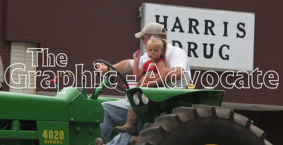 A young girl eats a sucker while riding a tractor during the 2016 Western Days parade. GRAPHIC-ADVOCATE PHOTO/ERIN SOMMERS
