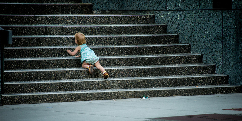 "September 10,<br /> <br /> What do you think when you look at this image?  Why is this child alone?  Where is the parent?  It can provoke such feelings.  Just looking at the toddler on the cold hard stairs of a major downtown building just feet away from a busy street would leave one to jump to conclusions and form an opinion on parenting.  That would be taking this situation out of context.  Context is defined as the circumstances that form the setting for an event, statement, or idea, and in terms of which it can be fully understood and assessed. <br /> <br /> This image was captured after observing a woman with a stroller and this toddler.  The mother or caregiver had to take the stroller up the stairs first and then come back for the toddler.  The toddler seeing the person of trust began crawling the stairs toward her.  This scene certainly captured my attention.  Since it was known the child was not in any danger the photo was set up and taken.  <br /> <br />  It seems like these days of the 24 hour news cycle, the news business thrives on reporting a story as soon as a situation unfolds which can lead to information that is taken out of context.  Jumping to conclusions before knowing the facts can lead to misinformation and unnecessary worry or angst.  It takes such discipline to keep from jumping to conclusions.   It is very easy to do this though. News organizations certainly do not own this.  Daily we are bombarded with information.   To be slow to judge and form opinions is difficult.  Fortunately, it is possible to do.  <br /> <br /> ""The greatest felony in the news business today is to be behind, or to miss a big story. So speed and quantity substitute for thoroughness and quality, for accuracy and context. The pressure to compete, the fear somebody else will make the splash first, creates a frenzied environment in which a blizzard of information is presented and serious questions may not be raised.""<br />  Carl Bernstein<br /> <br /> Peace."