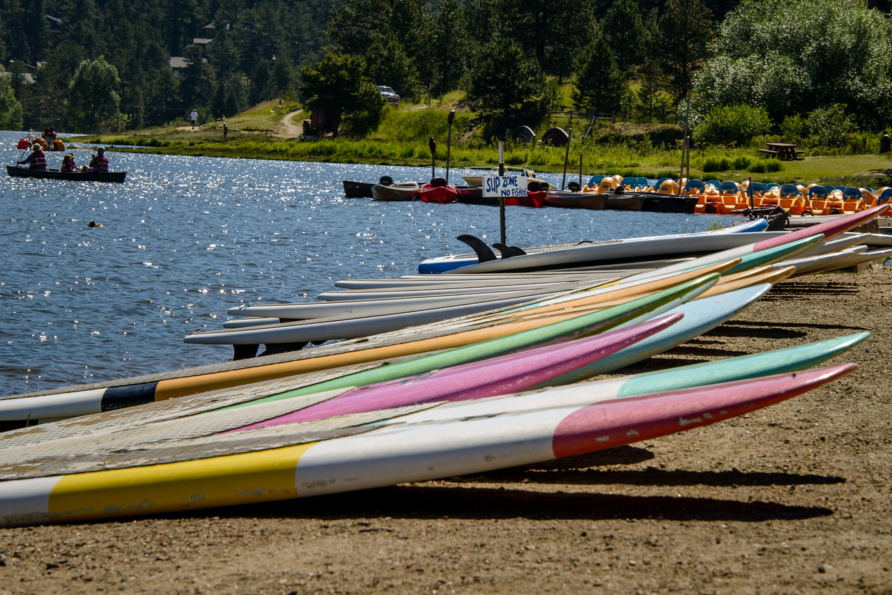 """July 23,<br /> <br /> Evergreen Lake is a true gift to the community.  It is a beautiful mountain lake  created by damming Bear Creek in 1927.  This lake sits at an altitude of 7200 ft.  It is used year round as a recreation area. In the winter one has a choice of ice fishing, ice skating or ice hockey and on New Year's Day the Polar Bear Plunge benefitting local charities is a popular event.  In the summer many enjoy the paddle boats, canoes , kayaks, sailboats,  or paddle boards.  Fishing is very popular in the summer whether it is by fly or lure.  Year round it is popular for birdwatching and hiking.  Just driving by the lake on the way to an event is a pleasure.  <br /> <br /> This image from the south shore captures the paddle boards that are waiting for their paddlers.  It is a wonderful lake to enjoy a family outing.  Kayaking on the lake is an activity my family enjoys.  It is fun to take guests for a ride on the beautiful waters and soak in the beautiful mountain scenery.  <br /> <br /> I am grateful to live in a community that values its resources and provides such pleasures for its citizens. <br /> <br /> """"A lake is the landscape's most beautiful and expressive feature. It is earth's eye; looking into which the beholder measures the depth of his own nature."""" ~Henry David Thoreau<br /> <br /> Peace."""