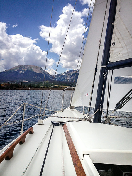 July 28,<br /> <br /> Sailing on Lake Dillon is a wonderful opportunity to enjoy the blue waters with the beautiful mountains in the background.  This body of water belongs to Denver and it is their largest reservoir.  The idea for this body of water came about in the early 1900's. The Denver Water Board acquired most of the property for this lake due to unpaid back taxes from residents who were devastated  by the Depression.  Denver made an offer they could not refuse. It must have been terrible to lose your property especially during the Depression.  In the early 1960's the Blue River was dammed and the water was diverted to Denver.<br />  <br /> The water originated just months ago from the abundant snow that draped these mountains and roadsides. This year due to the overwhelming snow fall, the reservoir is projected to be full for the first time since 2011.  Careful planning is done to release water into the river below to make room for the snowmelt. Flooding later in the season is a risk that is taken seriously.   <br /> <br /> This is a beautiful lake and many enjoy the waters by sailing, kayaking, paddle boarding, fishing,  in the summer and in the winter ice fishing, snow shoeing, and cross country skiing.  There is a  path around the lake that is great for bikers.  I am grateful for this beautiful water that provides so much pleasure to people of all ages.   I appreciate it even more due to the the pain of loss that many landowners experienced. <br /> <br /> It was a lovely day to be invited aboard our friends' sailboat.  Despite good planning and packing it turned out my camera was empty of the cards needed to store images.  Without spare cards I relied on my friend's i-phone.  I did have more fun since my camera was not between me and the scenery.  It is pretty amazing to enjoy these beautiful waters that were previously white powder, and it was so peaceful and enjoyable to feel the cool breeze and watch the changing shoreline.<br /> Sailing is certainly 