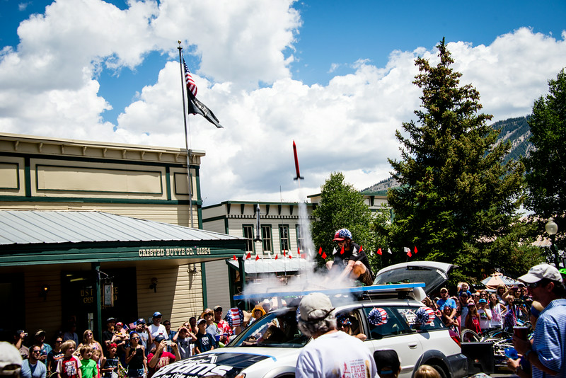 "July 4,<br /> <br /> Happy 4th of July!  Parades occur all over the country today, and here is a glimpse of a 'float' from the mountain town of Crested Butte's parade. This group represented a children's science camp and periodically would shoot off rockets that when at their crest in the sky burst into a small parachute of an American flag.   <br /> <br /> We first visited this unique mountain town 31 years ago over the Independence Day Holiday when our daughter was in a stroller.  My how this parade has grown!  <br /> <br /> I hope you are enjoying a day to your liking, and how blessed we are to live in America.<br /> <br /> ""As Mankind becomes more liberal, they will be more apt to allow that all those who conduct themselves as worthy members of the community are equally entitled to the protections of civil government. I hope ever to see America among the foremost nations of justice and liberality.""~George Washington<br /> <br /> Peace."