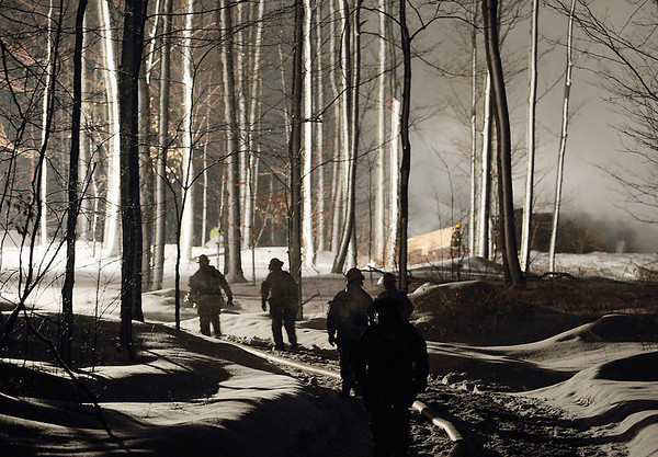 Record-Eagle/Keith King<br /> Firefighters walk up a driveway as they respond to a house fire Wednesday, March 9, 2011 in Leelanau County. Authorities continue to investigate what sparked a blaze that destroyed the home. Fire agencies across Leelanau County responded to a residential fire on Fouch Road in Solon Township. Nobody was injured, but fire destroyed the home, Cedar Fire Chief Dan Petroskey said.