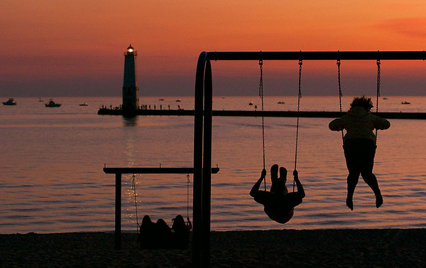 Record-Eagle/Douglas Tesner<br /> Beach goers enjoy the sunset on Lake Michigan with Frankfort Breakwater Light in the background.