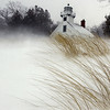 Record-Eagle/Tyler Sipe<br /> Blowing snow whips up dune grass near the Old Mission Lighthouse.
