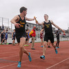 Record-Eagle/Keith King<br /> Traverse City Central's Anthony Berry, left, receives the baton from teammate Chris Brower in the 3,200-meter relay event during the Ken Bell Invitational Track Meet at Traverse City Central Senior High School.
