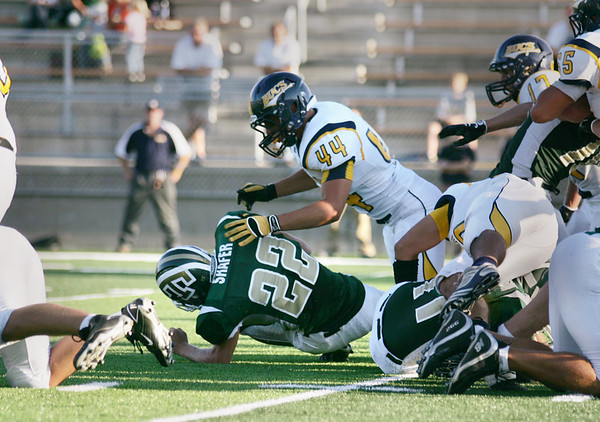 Record-Eagle/Keith King<br /> Ball carrier, Traverse City West's Zac Shafer, goes to the ground after a hard hit from Grand Haven's Jerry Westerman Friday, August 27, 2010 at Thirlby Field in Traverse City.